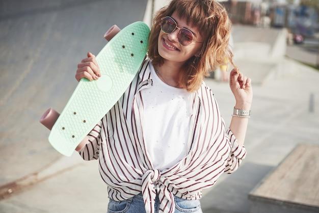 Mulher jovem e bonita elegante com um skate, em um lindo dia ensolarado de verão.