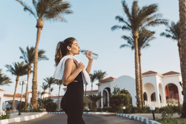 Mulher jovem e bonita elegante em sportswear bebendo água na rua em palmeiras, céu azul. humor alegre, olhos fechados, relaxamento, exercício, fitness