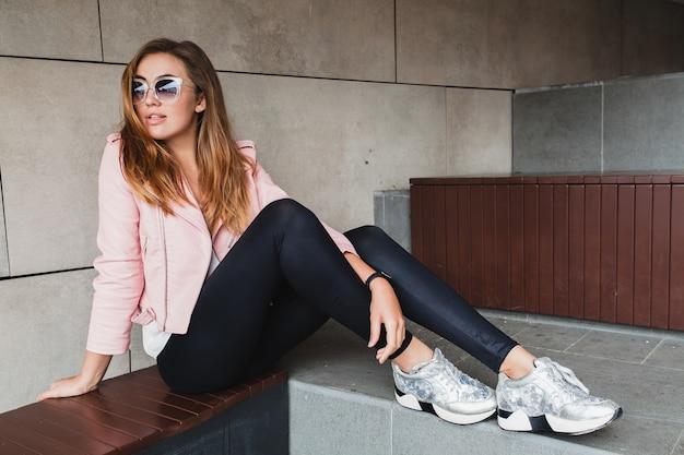 Mulher jovem e bonita elegante hipster em jaqueta de couro rosa
