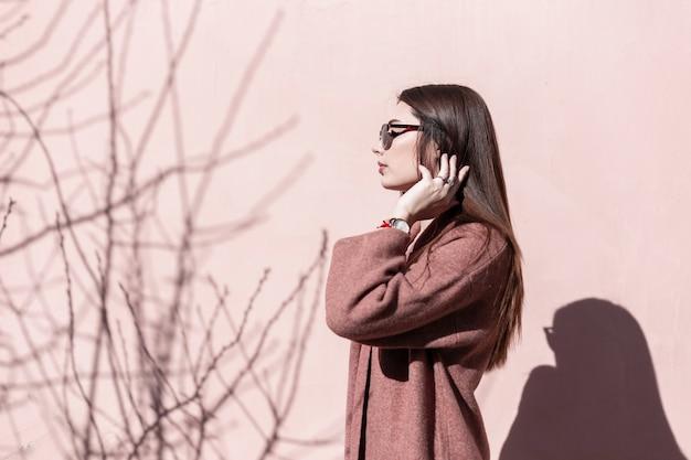 Mulher jovem e bonita elegante moderna em óculos de sol da moda posando de pé no sol perto de parede rosa vintage na cidade. garota sexy elegante em roupas elegantes endireita luxuosos cabelos longos. moda retrô.