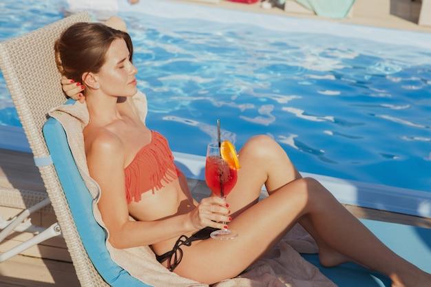 Mulher jovem e bonita elegante relaxante perto da piscina com um delicioso cocktail no copo dela. mulher relaxada, desfrutar de banhos de sol à beira da piscina
