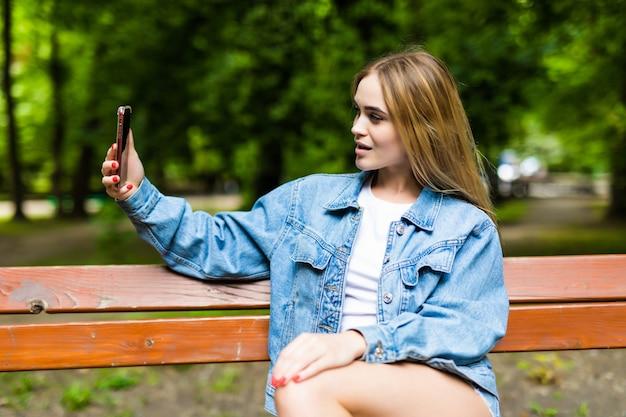 Mulher jovem e bonita elegante selfie no parque de verão