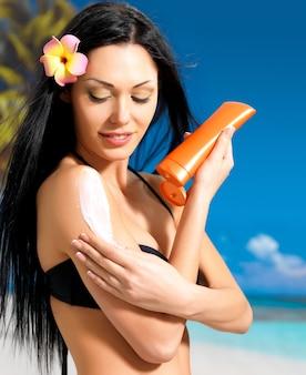 Mulher jovem e bonita em biquíni preto, aplicando protetor solar creme no corpo bronzeado.