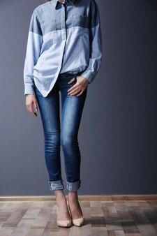 Mulher jovem e bonita em camisa e jeans na parede cinza