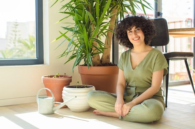 Mulher jovem e bonita em casa, com regador e plantas