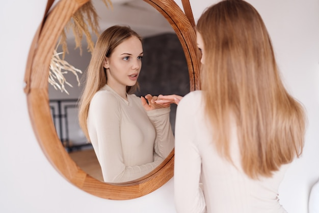 Mulher jovem e bonita em casa se olhando no espelho se divertindo