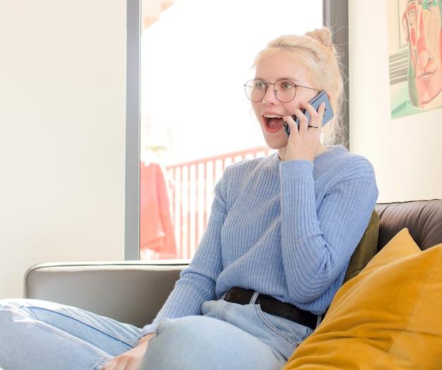Mulher jovem e bonita em casa usando um telefone