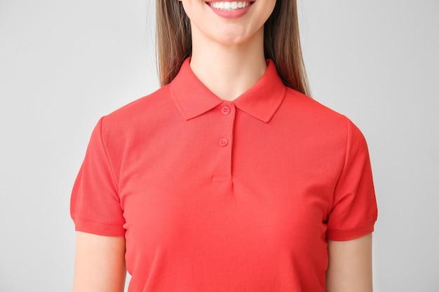 Mulher jovem e bonita em elegante camisa pólo na luz