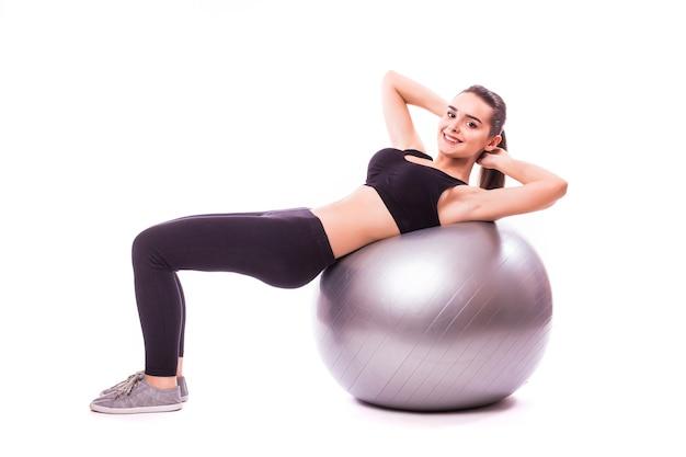 Mulher jovem e bonita em fitness com exercício de bola de ginástica, isolado no fundo branco