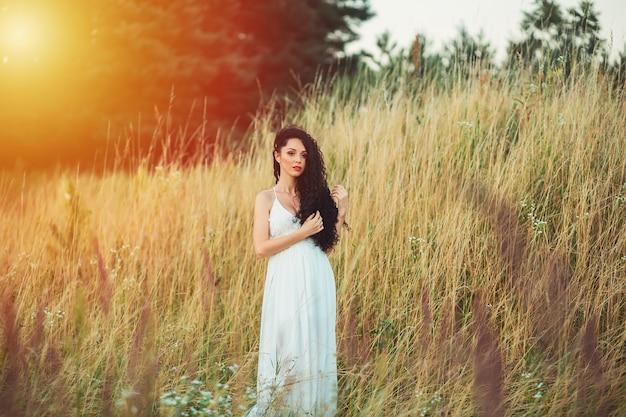 Mulher jovem e bonita em flores roxas ao ar livre