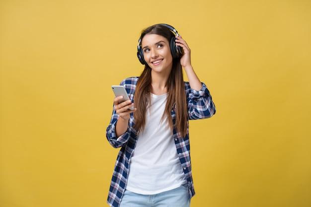 Mulher jovem e bonita em fones de ouvido, ouvindo música e cantando em fundo amarelo