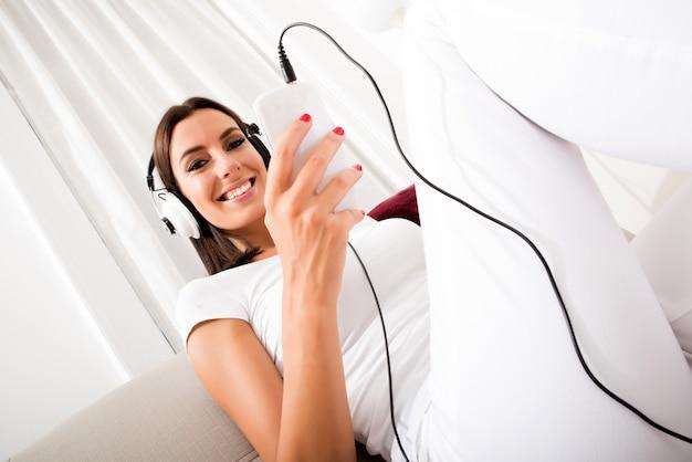 Mulher jovem e bonita em fones de ouvido, ouvindo música