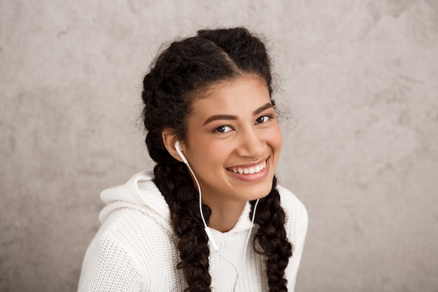Mulher jovem e bonita em fones de ouvido, sorrindo sobre parede bege