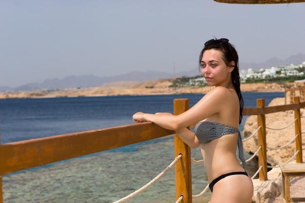 Mulher jovem e bonita em frente a uma cerca de madeira com cordões e o mar com corais e recifes contra o céu