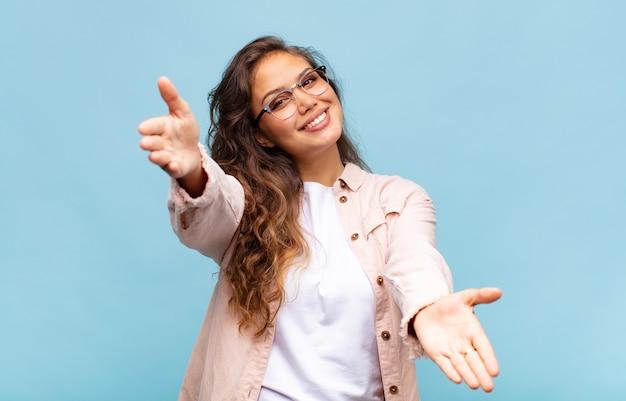 Mulher jovem e bonita em fundo azul com óculos