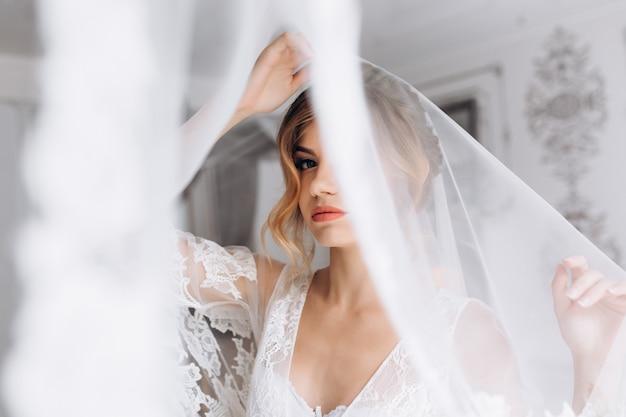 Mulher jovem e bonita em lingerie branca posa em roupão de seda branco no quarto de hotel brilhante