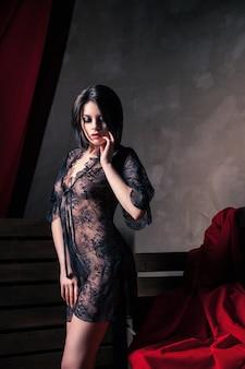 Mulher jovem e bonita em lingerie sexy no escuro