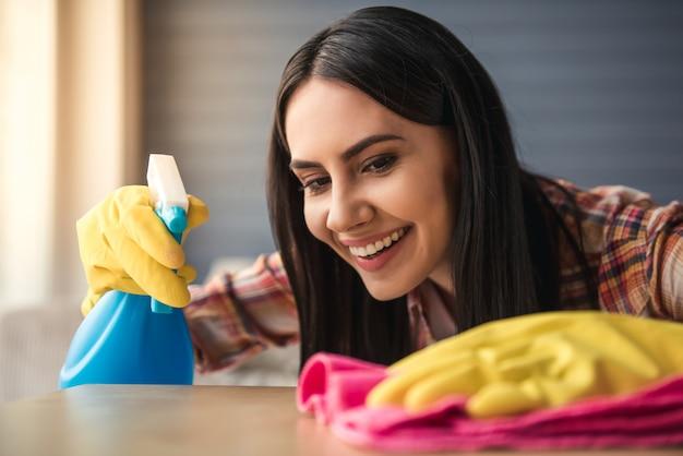 Mulher jovem e bonita em luvas de proteção está sorrindo e limpando