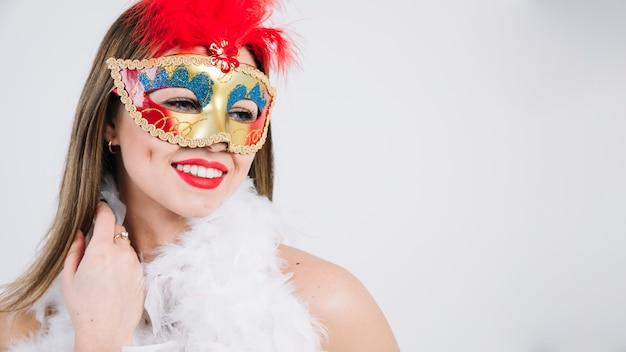 Mulher jovem e bonita em máscara de carnaval e boa de penas no fundo branco
