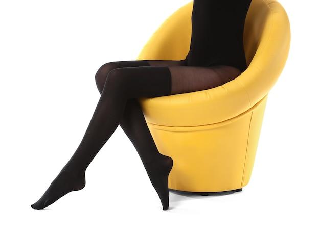 Mulher jovem e bonita em meia-calça sentada na cadeira contra o branco