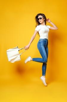 Mulher jovem e bonita em óculos de sol, camisa branca, calça jeans azul pulando com saco sobre o fundo amarelo