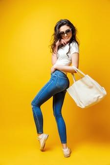 Mulher jovem e bonita em óculos de sol, camisa branca, jeans azul posando com saco