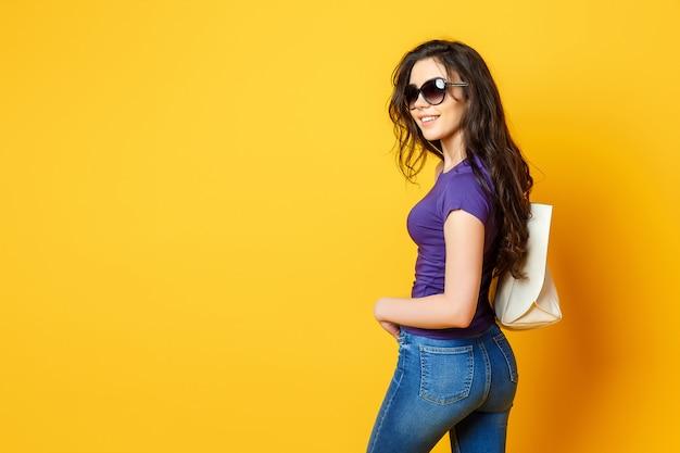Mulher jovem e bonita em óculos de sol, camisa roxa, jeans azul posando com saco em fundo amarelo