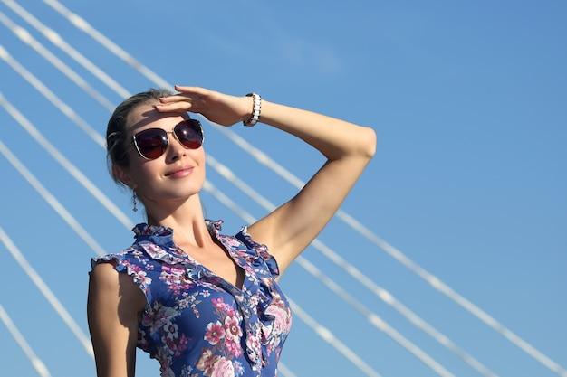 Mulher jovem e bonita em óculos de sol com a mão levantada olhando para o sol