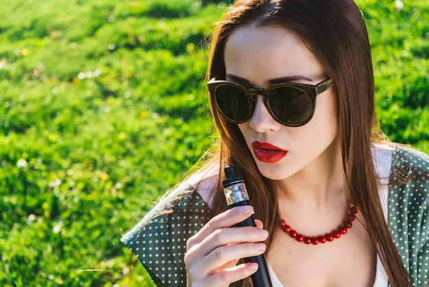 Mulher jovem e bonita em óculos de sol com cabelo comprido, sentado no gramado com grama verde brilhante, fumando. dia ensolarado