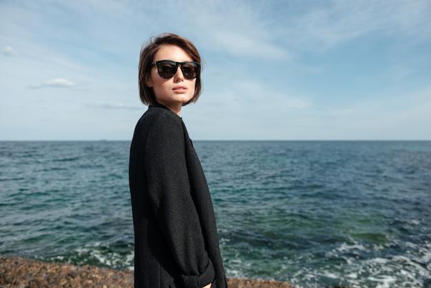 Mulher jovem e bonita em óculos de sol e casaco preto à beira-mar