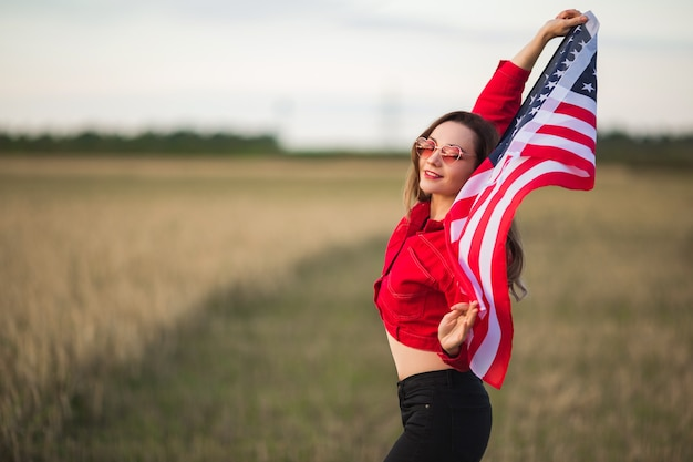 Mulher jovem e bonita em óculos de sol rosa com bandeira americana