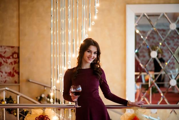 Mulher jovem e bonita em pé com uma taça de vinho nas mãos