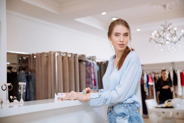 Mulher jovem e bonita em pé lendo uma revista em uma loja de roupas