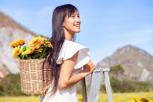 Mulher jovem e bonita em pé na escada para relaxar em um campo de girassóis em um vestido branco.