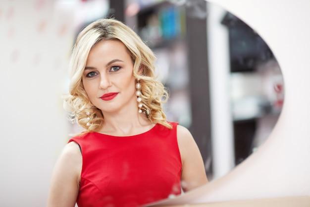 Mulher jovem e bonita em pé na frente de um espelho no vestido vermelho. menina sorridente caucasiana, olhando o reflexo no espelho. fechar o retrato da mulher sorridente
