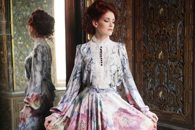 Mulher jovem e bonita em pé na sala do palácio com espelho.