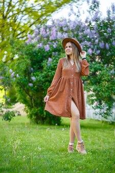 Mulher jovem e bonita em pé no contexto de arbustos de lilases. menina de chapéu marrom e vestido
