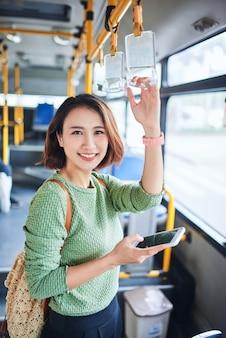 Mulher jovem e bonita em pé no ônibus da cidade e falando no celular.