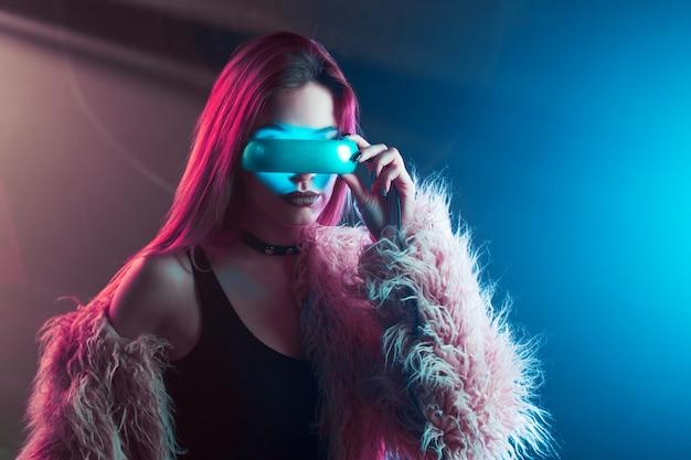 Mulher jovem e bonita em realidade virtual, o estilo cyberpunk, luz de neon, conceito de vr