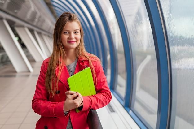 Mulher jovem e bonita em roupa casual segurando um tablet laptop em um prédio urbano