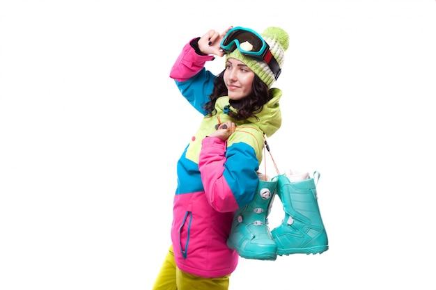Mulher jovem e bonita em roupa de esqui e óculos de esqui azul botas de neve