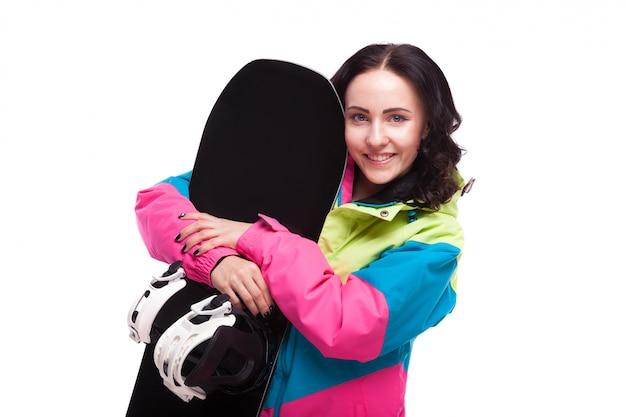 Mulher jovem e bonita em roupa de esqui e segurar snowboard