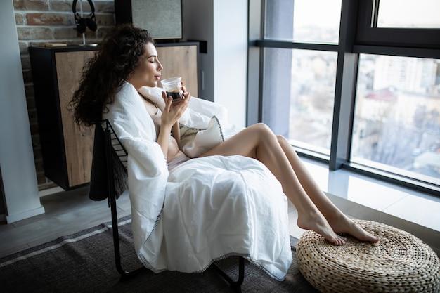 Mulher jovem e bonita em roupa interior sentada ao lado de uma janela a desfrutar de uma chávena de café pela manhã