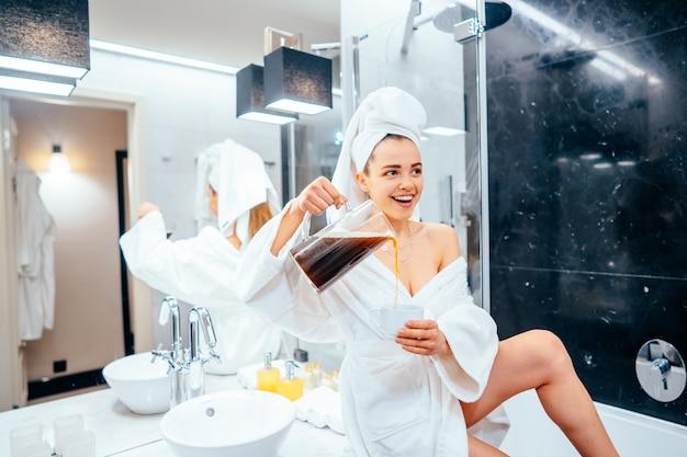 Mulher jovem e bonita em roupão e toalha na cabeça, sentado em uma banheira