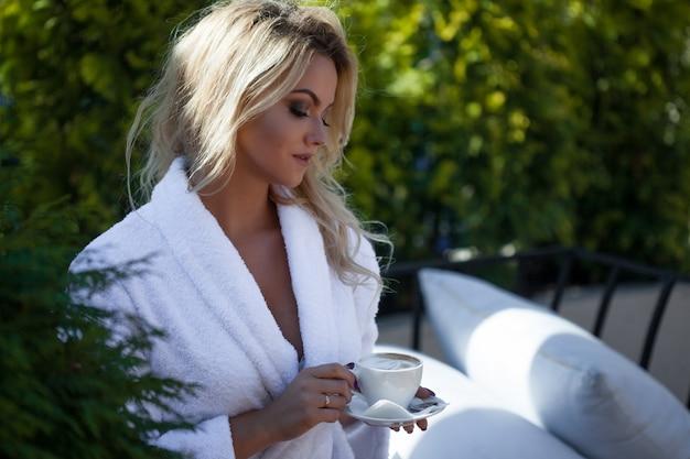 Mulher jovem e bonita em roupão sentado no terraço e beber café