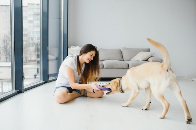 Mulher jovem e bonita em roupas casuais abraçando seu amado cachorrão branco na sala de estar