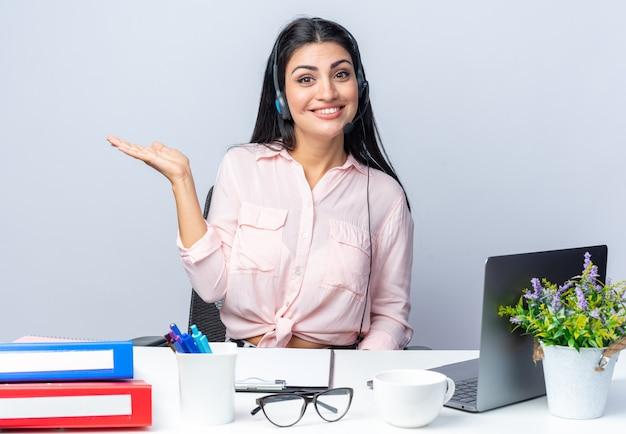 Mulher jovem e bonita em roupas casuais com fones de ouvido e microfone, parecendo sorridente confiante apresentando-se com o braço sentado à mesa com laptop sobre fundo branco, trabalhando no escritório