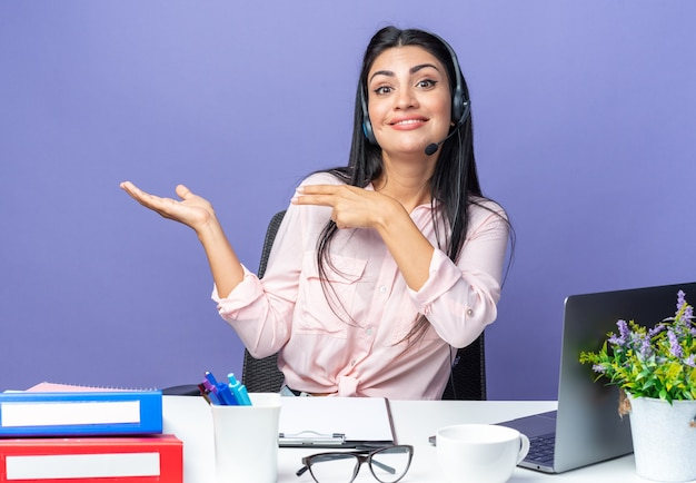 Mulher jovem e bonita em roupas casuais, usando fone de ouvido com microfone, sorrindo, apresentando-se com o braço da mão, sentado à mesa com o laptop sobre a parede azul, trabalhando no escritório