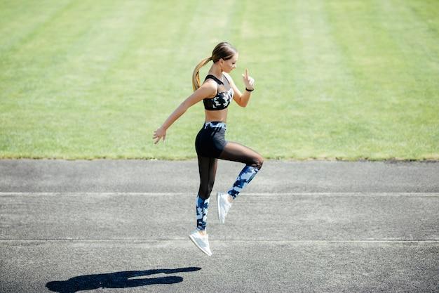 Mulher jovem e bonita em roupas esportivas, aquecimento com exercícios de salto durante o exercício ao ar livre.