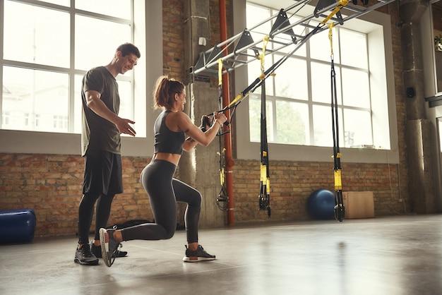 Mulher jovem e bonita em roupas esportivas fazendo exercícios trx na academia enquanto seu personal trainer